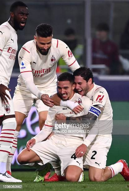Milan's Algerian midfielder Ismael Bennacer celebrates with AC Milan's French forward Olivier Giroud and AC Milan's Italian defender Davide Calabria...