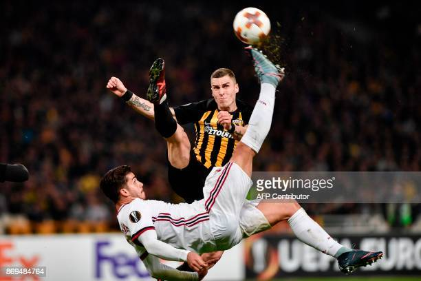 Milan's Andre Silva vies for the ball with AEK's Ognjen Vranjes during the UEFA Europa League Group D football match between AEK Athens and AC Milan...