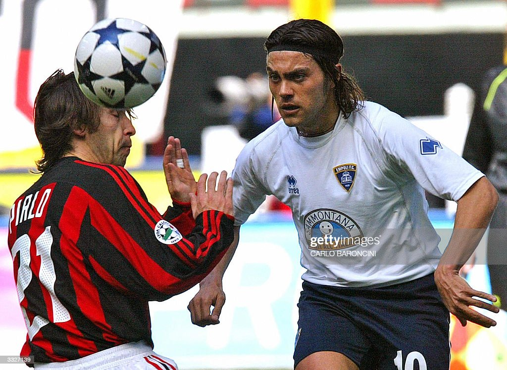 AC Milan's Andrea Pirlo (L) in action with Francesco Tavano (R) of Empoli during their Italian Serie A football match at Empoli's stadium, 10 April 2004. AFP PHOTO/Carlo BARONCINI