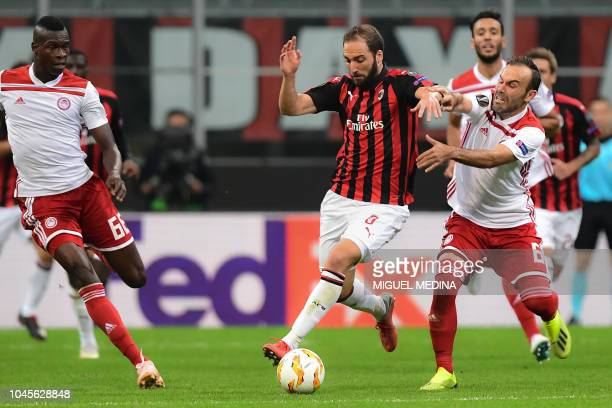 AC Milan's Argentine forward Gonzalo Higuain outruns Olympiakos' Israeli midfielder Bebars Natcho during the Europa League Group F football match...