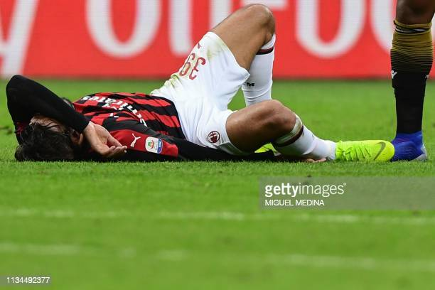 AC Milan's Brazilian midfielder Lucas Paqueta reacts in pain on the pitch following an ankle injury during the Italian Serie A football march AC...