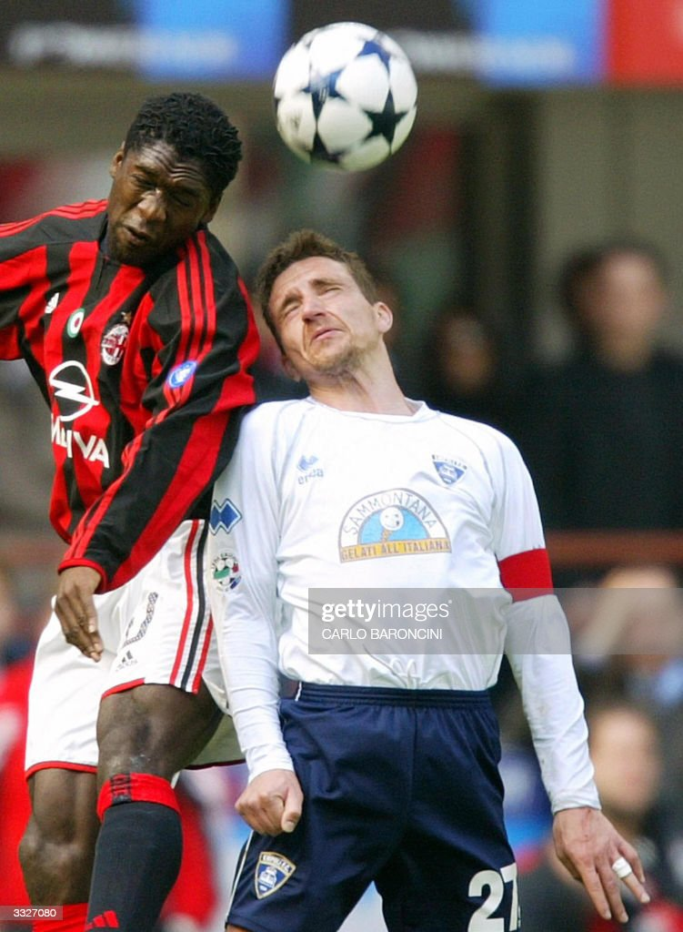 AC Milan's Clarence Seedorf (L) jumps for the ball with Fabrizio Ficini of Empoli during their Italian Serie A football match at Empoli stadium 10 April 2004. AFP PHOTO/Carlo BARONCINI