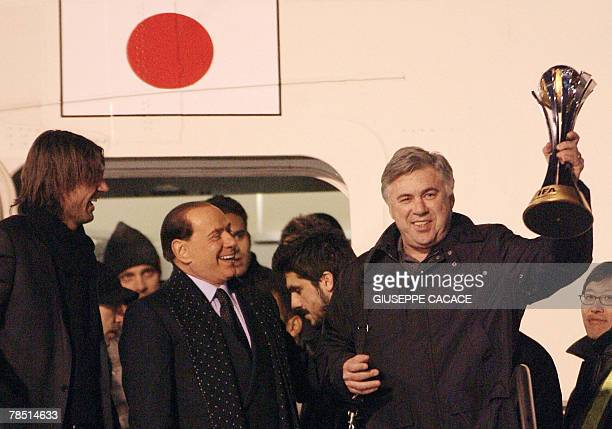 C Milan's coach Carlo Ancelotti lifts the FIFA Club World cup trophy flanked by AC Milan's president and former Italian prime minister Silvio...