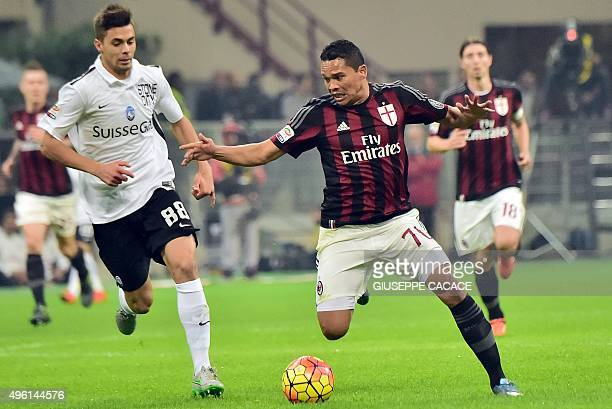 AC Milan's Colombian forward Carlos Bacca challenges Atalanta's Italian midfielder Alberto Grassi during the Serie A football match between AC Milan...