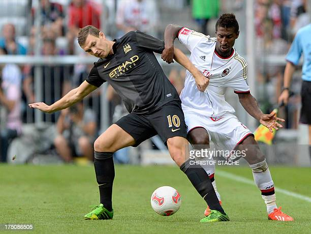 AC Milan's Colombian midfielder Kevin Constant and Manchester City's Bosnian striker Edin Dzeko vie for the ball during the Audi Cup football match...