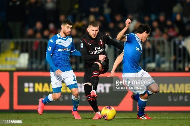 AC Milan's Croatian forward Ante Rebic vies with Brescia's Italian defender Stefano Sabelli and Brescia's Italian defender Andrea Cistana during the...