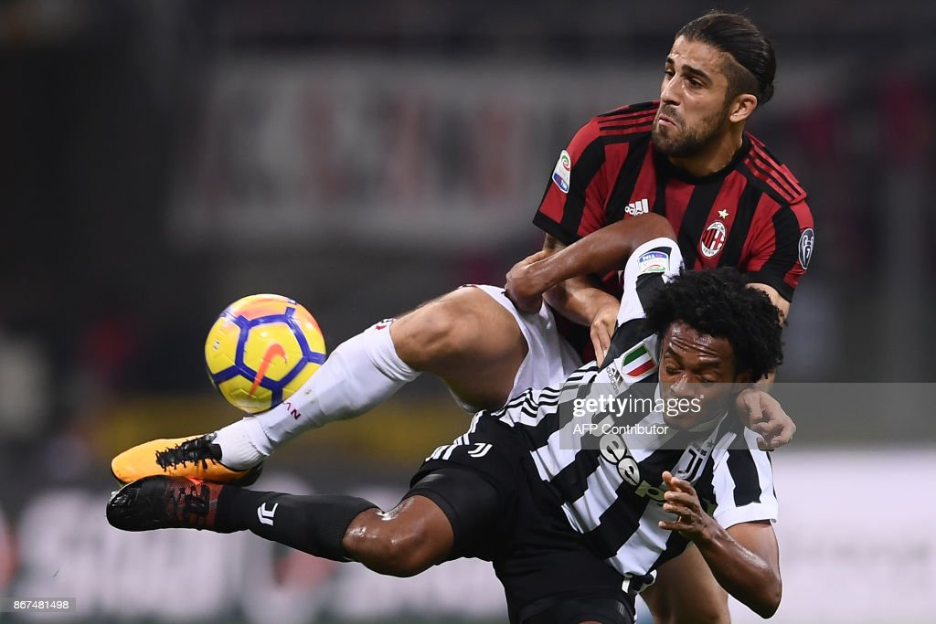 AC Milan's defender Ricardo Rodriguez from Switzerland (top) fights for the ball with Juventus' midfielder Juan Cuadrado from Colombia during the Italian Serie A football match AC Milan Vs Juventus on October 28, 2017 at the 'Giuseppe Meazza' Stadium in Milan. /