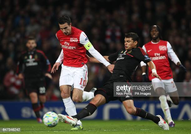 AC Milan's Emiliano Thiago Silva and Arsenal's Robin van Persie battle for the ball