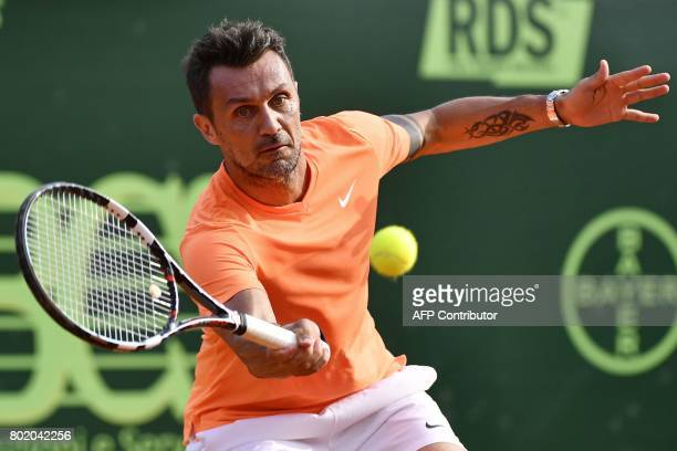 AC Milan's former player Paolo Maldini returns the ball during the men's doubles tennis match with his partner Stefano Landonio against Poland's...