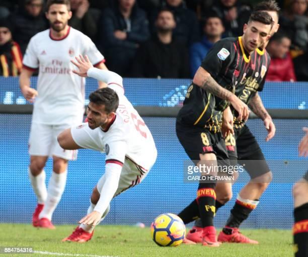 AC Milan's forward Fernandez Suso falls as fighting for the ball with Benevento's Italian midfielder Danilo Cataldi during the Italian Serie A...