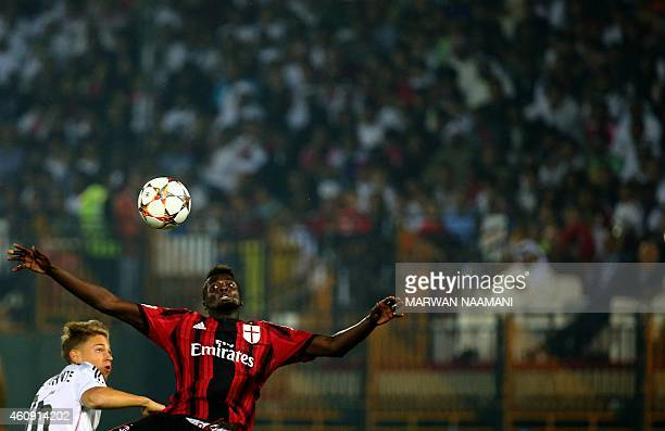AC Milan's forward Mbaye Niang vies for the ball against Real Madrid's Marcos Llorente during their friendly football match on December 30 2014 at...