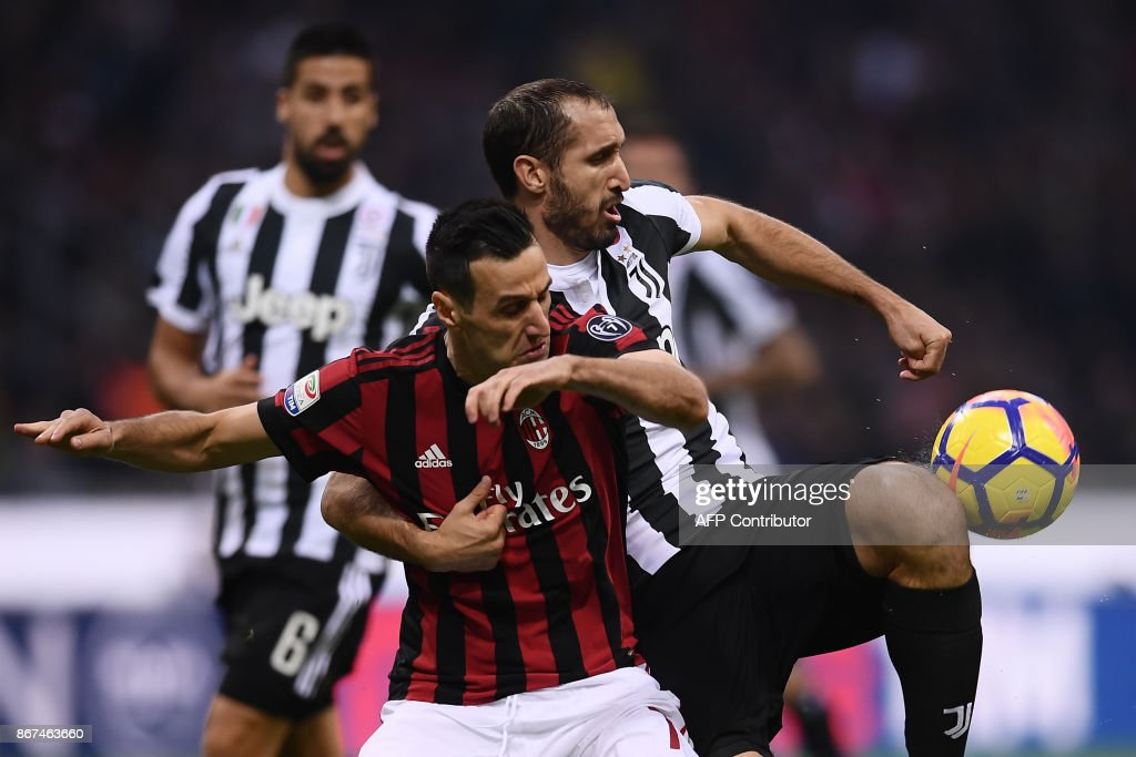 AC Milan's forward Nikola Kalinic from Croatia (C) fights for the ball with Juventus' defender Giorgio Chiellini during the Italian Serie A football match AC Milan Vs Juventus on October 28, 2017 at the 'Giuseppe Meazza' Stadium in Milan. /