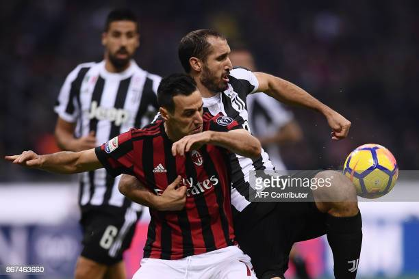 AC Milan's forward Nikola Kalinic from Croatia fights for the ball with Juventus' defender Giorgio Chiellini during the Italian Serie A football...