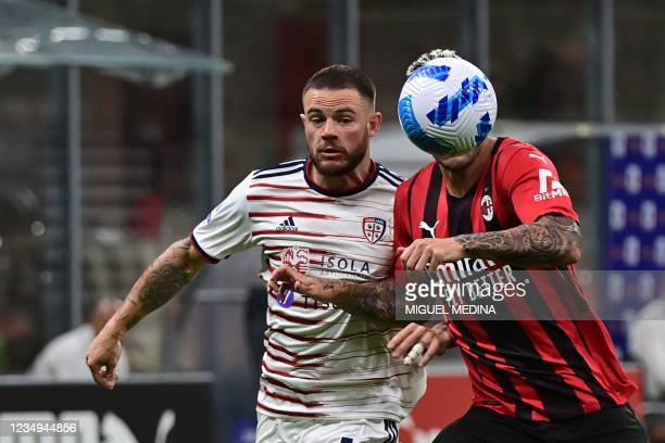 Milan's French defender Theo Hernandez challenges Cagliari's Uruguayan midfielder Nahitan Nandez during the Italian Serie A football match between AC...