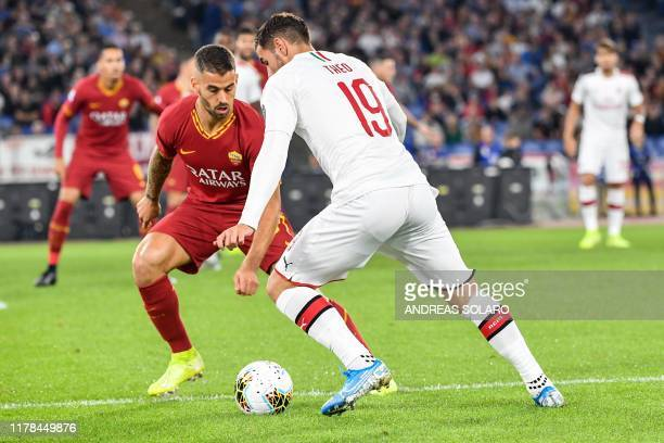 AC Milan's French defender Theo Hernandez is challenged by AS Roma's Italian defender Leonardo Spinazzola during the Italian Serie A football match...