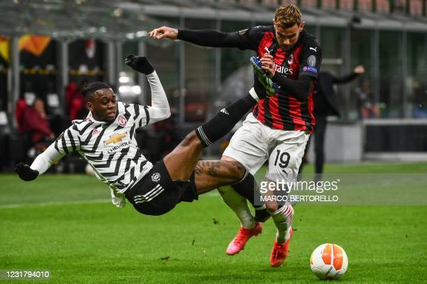 Milan's French defender Theo Hernandez tackles Manchester United's England's defender Aaron Wan-Bissaka during the UEFA Europa League round of 16...