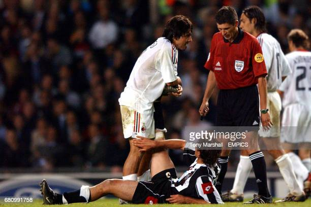 AC Milan's Gennaro Gattuso helps out as Juventus' Alessio Tacchinardi suffers from cramp as referee Markus Merk looks on