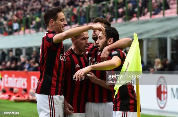 AC Milan's German midfielder Hakan Calhanoglu is congratulated by teammates after scoring during the Italian Serie A football match AC Milan vs AC...