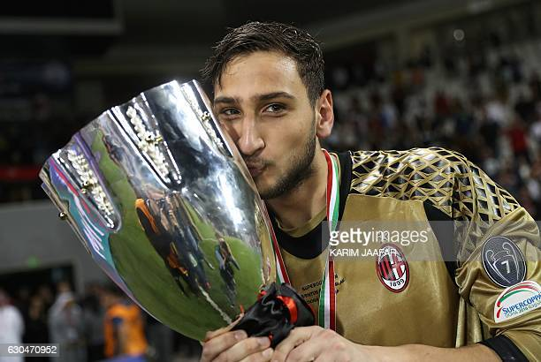 AC Milan's goalkeeper Gianluigi Donnarumma poses with the trophy after winning the Italian Super Cup final match between AC Milan and Juventus in...