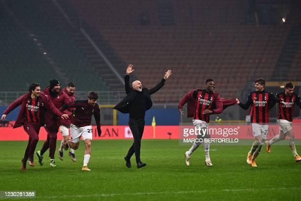 Milan's Italian coach Stefano Pioli celebrates with AC Milan's Portuguese forward Rafael Leao , AC Milan's Italian forward Daniel Maldini and AC...