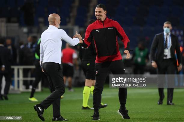 Milan's Italian coach Stefano Pioli celebrates with AC Milan's Swedish forward Zlatan Ibrahimovic after AC Milan secured their qualification for the...