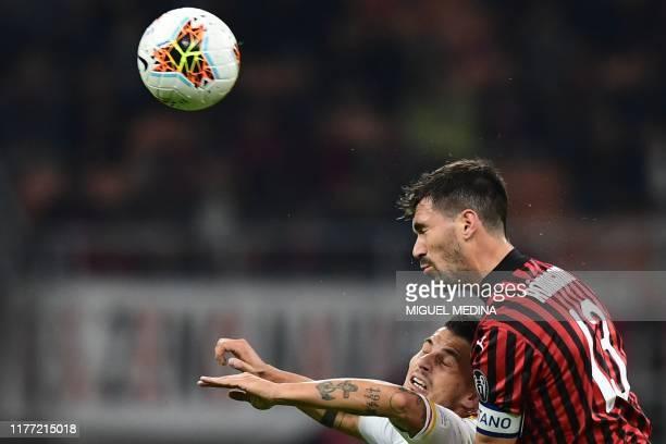 Milan's Italian defender Alessio Romagnoli and Lecce's Italian forward Filippo Falco go for a header during the Italian Serie A football match AC...