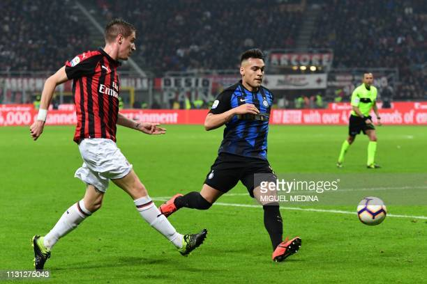 AC Milan's Italian defender Andrea Conti centres past Inter Milan's Argentine forward Lautaro Martinez during the Italian Serie A football match AC...