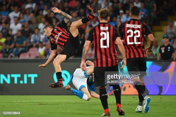 AC Milan's Italian defender Davide Calabria and Napoli's Portuguese defender Mario Rui fall after going for a header during the Italian Serie A...