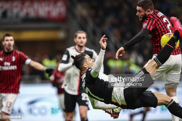 AC Milan's Italian defender Davide Calabria touches the ball with his arm as Juventus' Portuguese forward Cristiano Ronaldo performs an acrobatic...