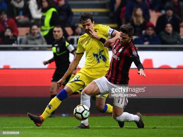 AC Milan's Italian forward Fabio Borini vies with Chievo's Serbian midfielder Ivan Radovanovic during the Italian Serie A football match AC Milan vs...