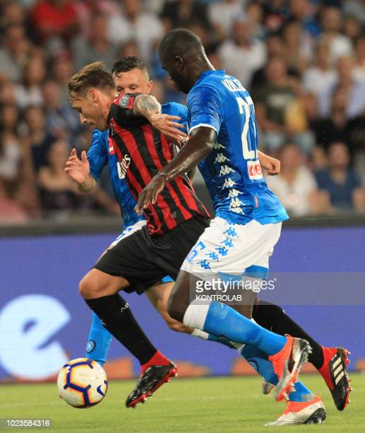 Milan's Italian forward Fernandez Suso fights for the ball with Napoli's French defender Kalidou Koulibaly during the Italian Serie A football match...