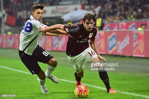 AC Milan's Italian midfielder Andrea Poli challenges Atalanta's Italian midfielder Alberto Grassi during the Serie A football match between AC Milan...