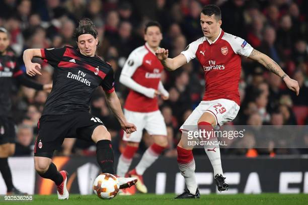 AC Milan's Italian midfielder Riccardo Montolivo vies with Arsenal's Swiss midfielder Granit Xhaka during the UEFA Europa League round of 16...