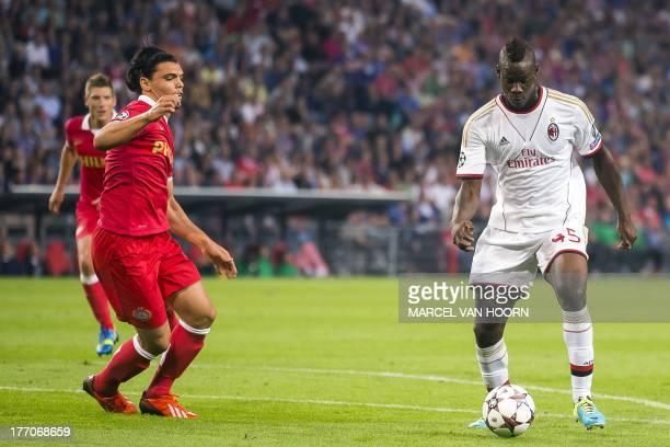 Milan's Italian striker Mario Balotelli vies with PSV Eindhoven's Dutch defender Karim Rekik during the Champions League play-off football match...