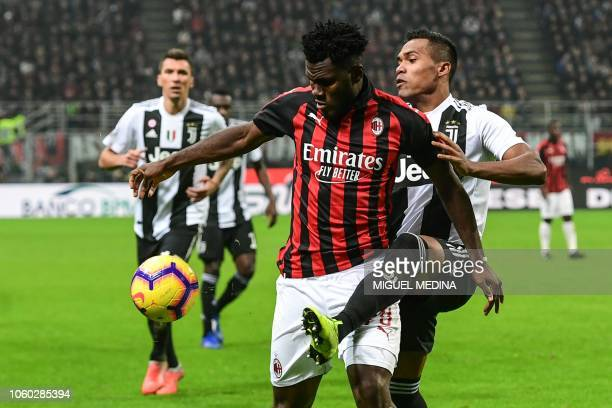 AC Milan's Ivorian midfielder Franck Kessie holds off Juventus' Brazilian defender Alex Sandro during the Italian Serie A football match AC Milan vs...