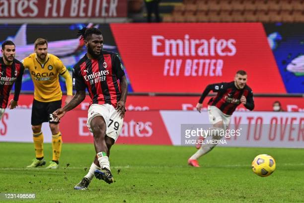 Milan's Ivorian midfielder Franck Kessie shoots to score a last minute penalty during the Italian Serie A football match AC Milan vs Udinese on March...