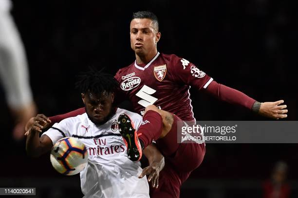 Milan's Ivorian midfielder Franck Kessie vies for the ball with Torino's Italian defender Armando Izzo during the Italian Serie A football match...