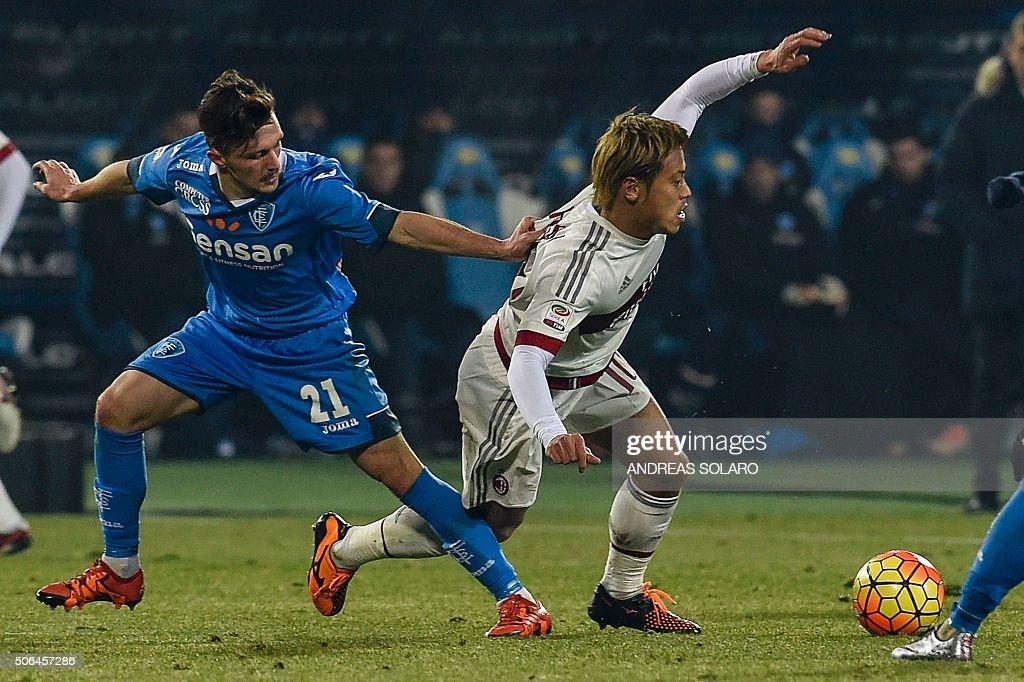 AC Milan's Japanese midfielder Keisuke Honda (R) vies with Empoli's Portuguese defender Mario Rui during the Italian Serie A football match Empoli vs AC Milan, on January 23, 2016 at the Carlo Castellani stadium in Empoli. / AFP / ANDREAS