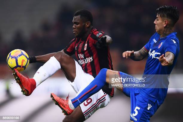 AC Milan's midfielder Franck Kessie from Ivory Coast fights for the ball with Bologna's defender Erick Pulgar during the Italian Serie A football...