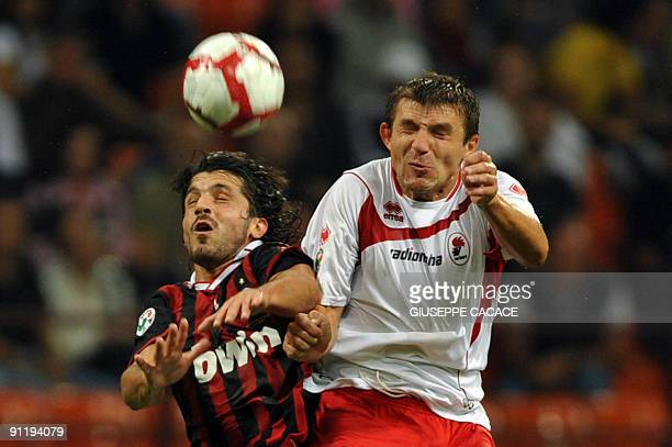 Milan's midfielder Gennaro Ivan Gattuso jumps for the ball with Bari's forward Vitali Kutuzov during their Serie A football match AC Milan vs Bari at...