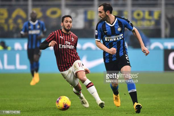 AC Milan's midfielder Hakan Calhanoglu from Turkey fights for the ball with Inter Milan's defender Diego Godin from Uruguay during the Italian Serie...