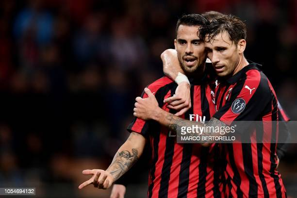 AC Milan's midfielder Suso from Spain celebrates after scoring with his teammate AC Milan's midfielder Lucas Biglia from Argentina during the Italian...