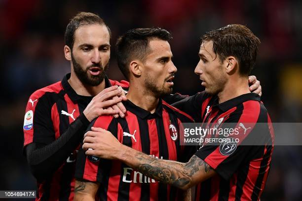 AC Milan's midfielder Suso from Spain celebrates after scoring with his teammate AC Milan's midfielder Lucas Biglia from Argentina and AC Milan's...
