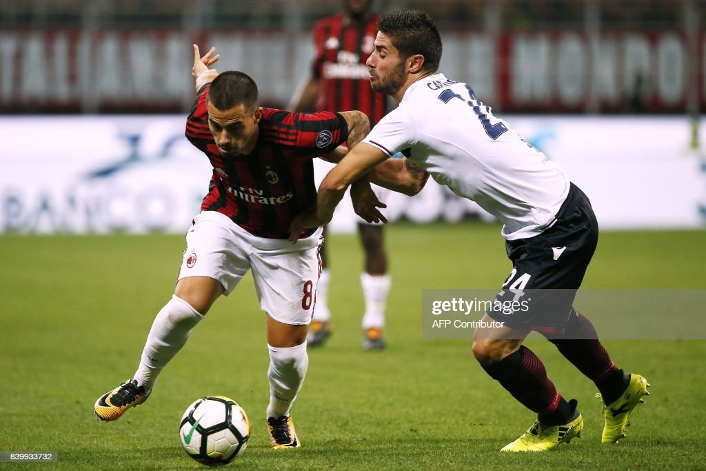 AC Milan's midfielder Suso from Spain (L) vies with Cagliari's defender Marco Capuano during the Italian Serie A football match AC Milan Vs Cagliari on August 27, 2017 at the 'Giuseppe Meazza' Stadium in Milan. / AFP PHOTO / Marco BERTORELLO