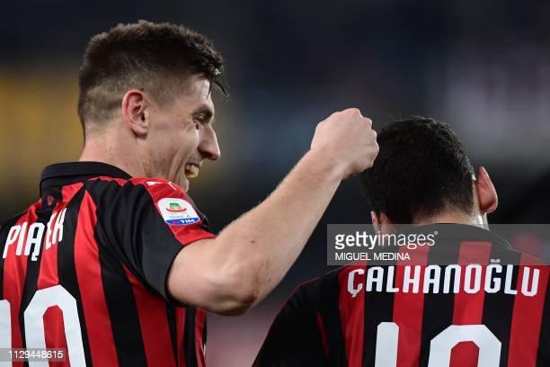 AC Milan's Polish forward Krzysztof Piatek celebrates with AC Milan's Turkish midfielder Hakan Calhanoglu after scoring during the Italian Serie A...