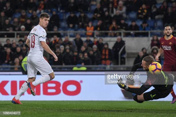 AC Milan's Polish forward Krzysztof Piatek shoots to open the scoring past AS Roma Swedish goalkeeper Robin Olsen during the Italian Serie A football...