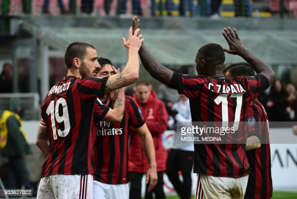 AC Milan's Portuguese forward Andre Silva is congratulated by AC Milan's Captain Italian defender Leonardo Bonucci AC Milan's Colombian defender...