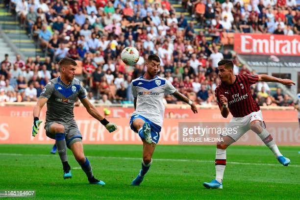 AC Milan's Portuguese forward Andre Silva vies with Brescia's Italian midfielder Stefano Sabelli and Brescia's Finnish goalkeeper Jesse Joronen...