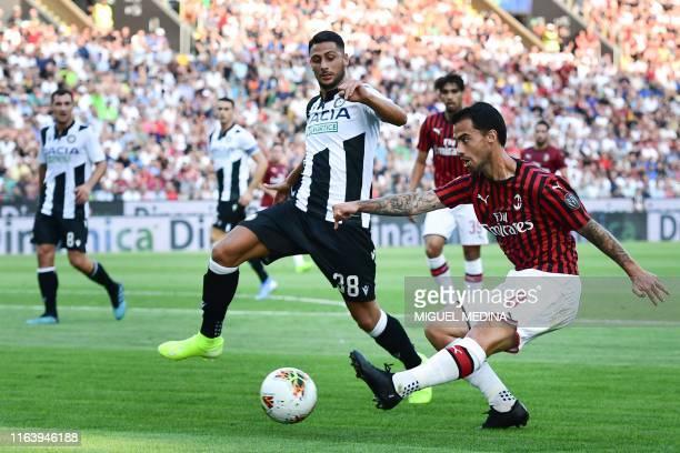 AC Milan's Spanish forward Suso centres past Udinese's Italian midfielder Rolando Mandragora during the Italian Serie A football match Udinese vs AC...