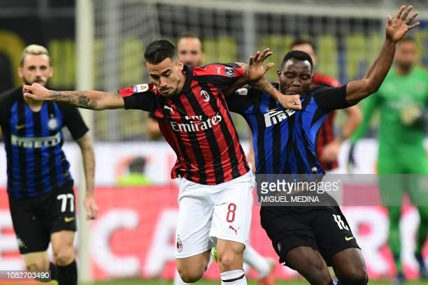 AC Milan's Spanish forward Suso holds off Inter Milan's Ghanaian midfielder Kwadwo Asamoah during the Italian Serie A football match Inter Milan vs...